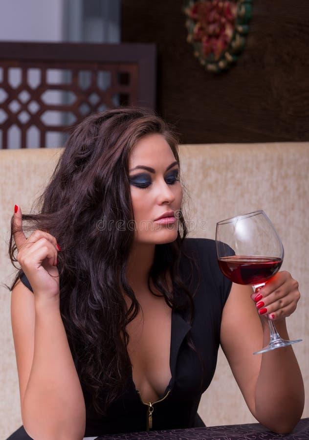 Uma jovem mulher está guardando um vidro do vinho imagem de stock royalty free