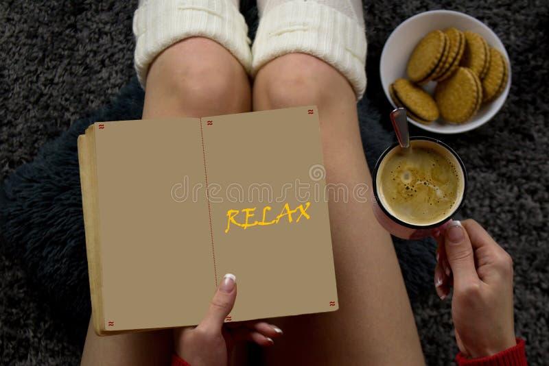 Uma jovem mulher está lendo um livro, café bebendo e está comendo biscoitos imagens de stock
