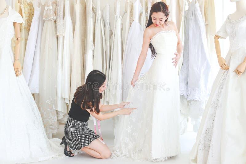 Uma jovem mulher está tentando o vestido de casamento no estúdio, desenhista é tão imagens de stock royalty free