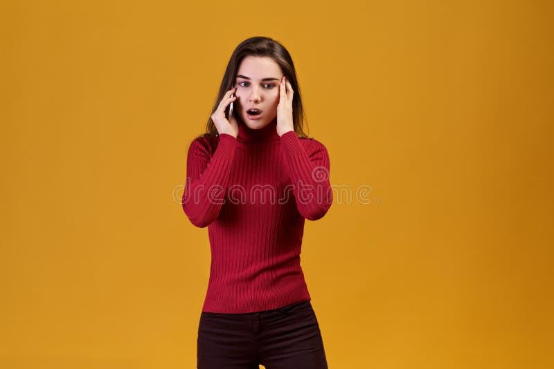 Uma jovem mulher fala no telefone, a notícia pô-la em um choque O especialista novo olha afastado fotos de stock royalty free