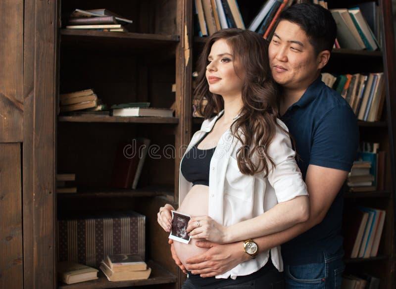 Uma jovem mulher grávida e um homem estão estando de lado a lado fotos de stock royalty free