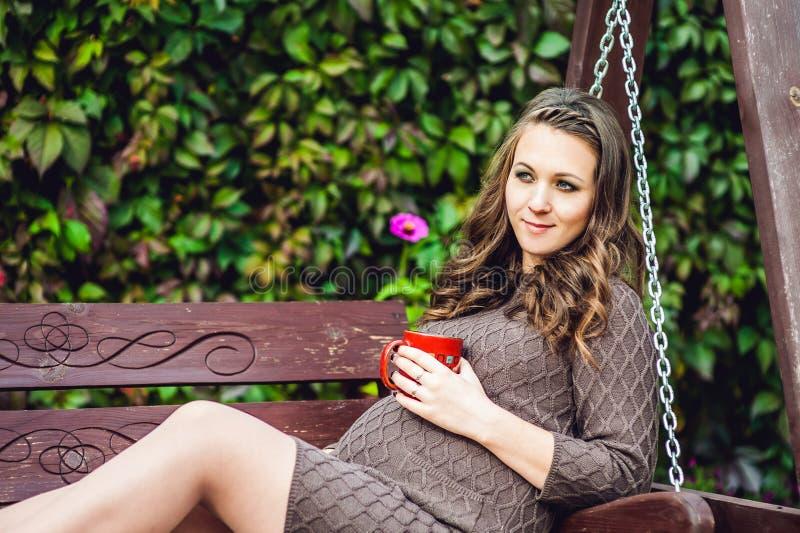 Uma jovem mulher grávida que senta-se em um balanço, com um copo do chá Mulher gravida que relaxa no parque imagem de stock