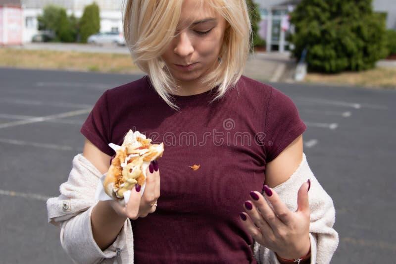 Uma jovem mulher guarda um cachorro quente mordido imagem de stock royalty free