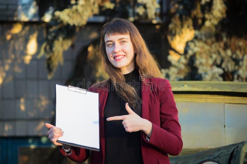 Uma jovem mulher, guardando um papel vazio em suas mãos foto de stock