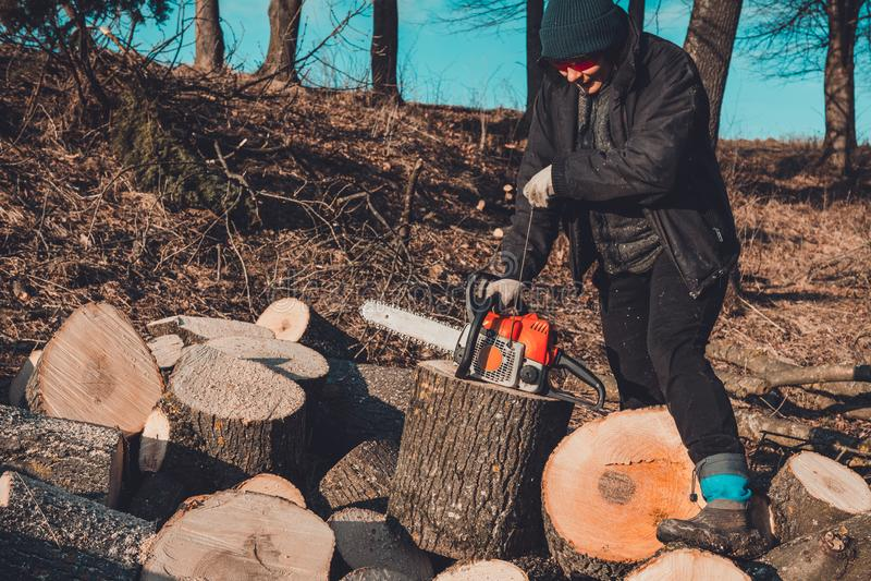 Uma jovem mulher lan?a uma serra de cadeia para cortar a madeira no campo fotos de stock