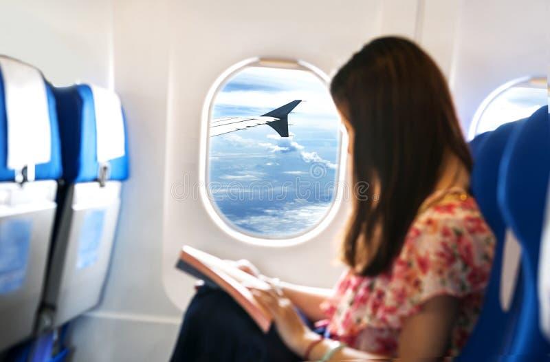 Uma jovem mulher a ler no plano fotos de stock royalty free