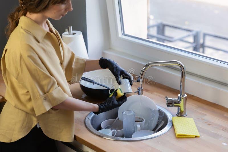 Uma jovem mulher limpa na cozinha, lavando pratos fotografia de stock royalty free