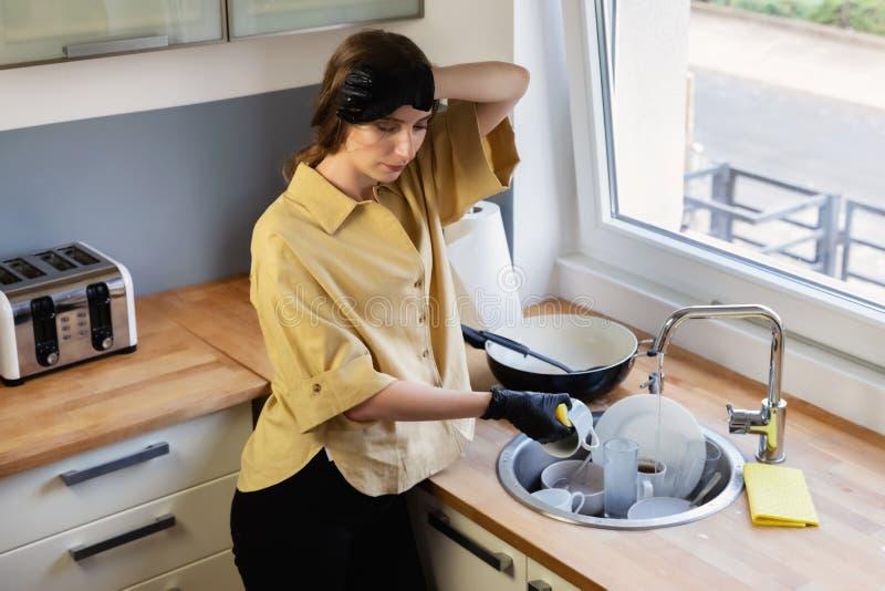 Uma jovem mulher limpa na cozinha, lavando pratos foto de stock