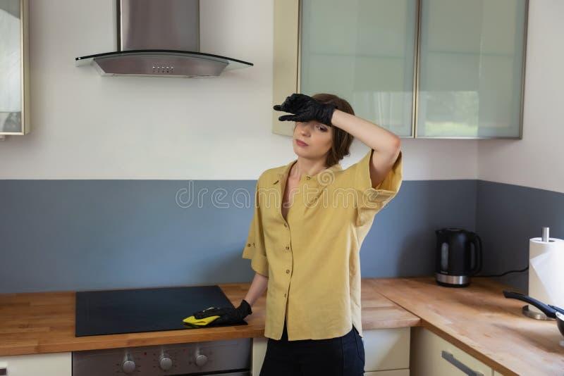 Uma jovem mulher limpa na cozinha, lavando pratos foto de stock royalty free