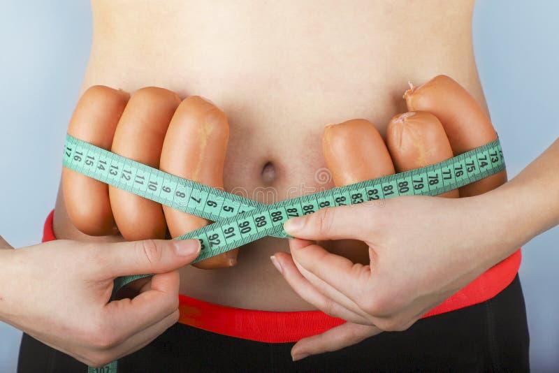 Uma jovem mulher mede sua cintura por uma fita de medição foto de stock