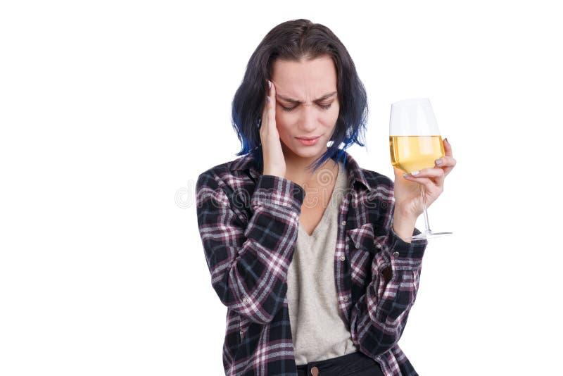 Uma jovem mulher, mostrando uma dor de cabeça, e realizando um vidro do vinho em sua mão Isolado no branco imagens de stock royalty free