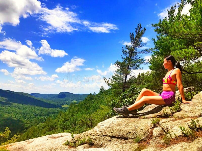 Uma jovem mulher na parte superior da montanha imagens de stock royalty free