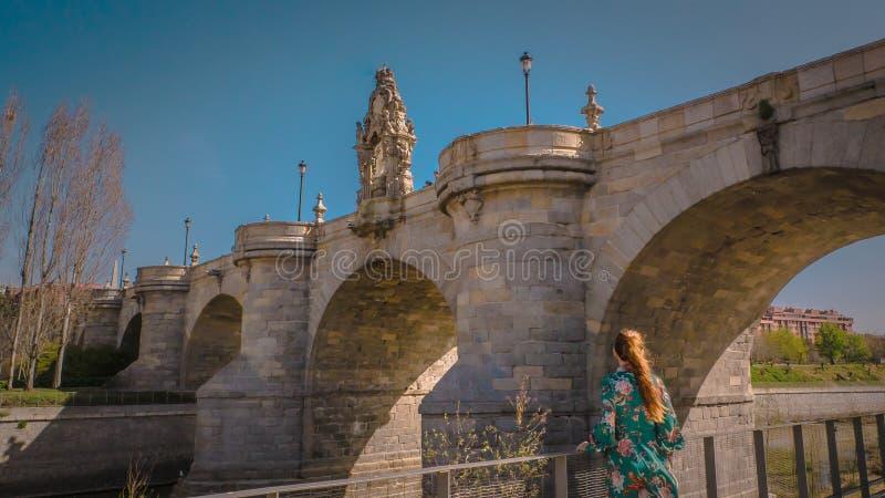 Uma jovem mulher na ponte medieval de Toledo no parque do Rio do Madri na Espanha imagem de stock