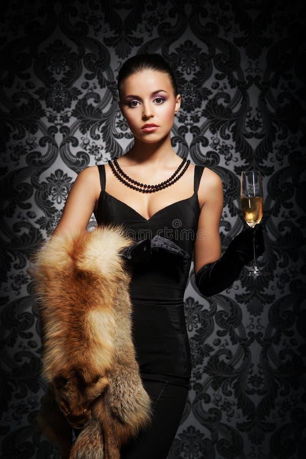 Uma jovem mulher na roupa luxuoso que guarda o champanhe imagem de stock