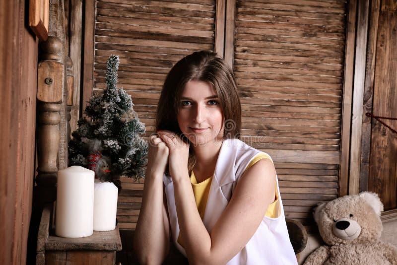 Uma jovem mulher no branco senta-se em uma casa de campo em antecipação ao Natal imagens de stock royalty free