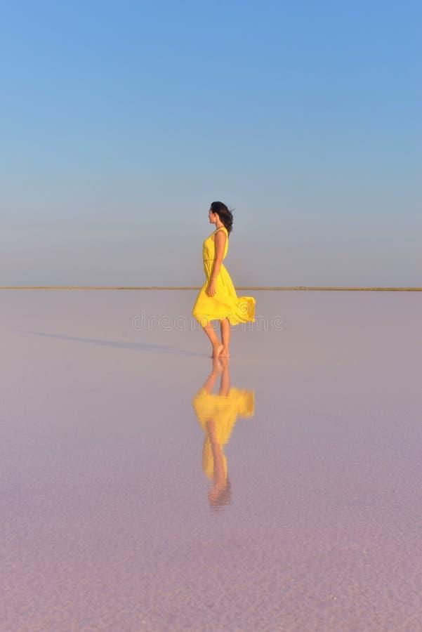 Uma jovem mulher no meio de um lago de sal cor-de-rosa está em um vestido amarelo brilhante e encontra o por do sol fotografia de stock royalty free