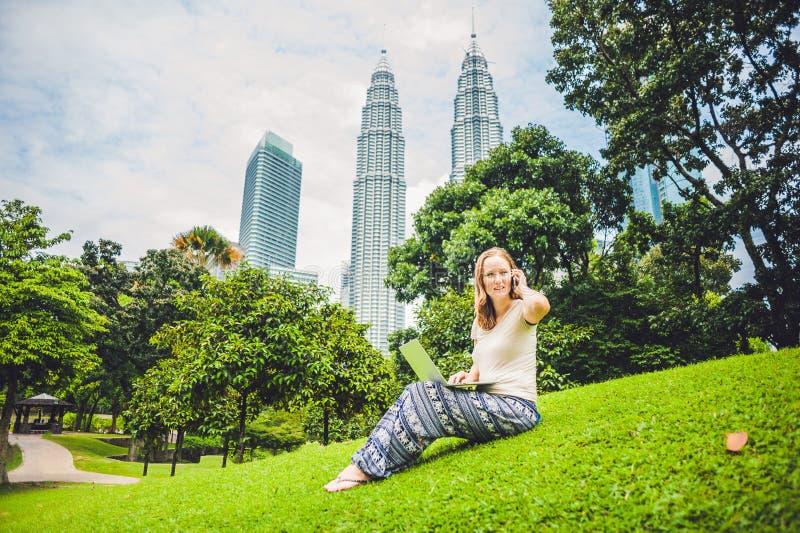 Uma jovem mulher no vestido ocasional usando o portátil em um parque tropical no fundo dos arranha-céus Conceito do escritório mó fotografia de stock royalty free