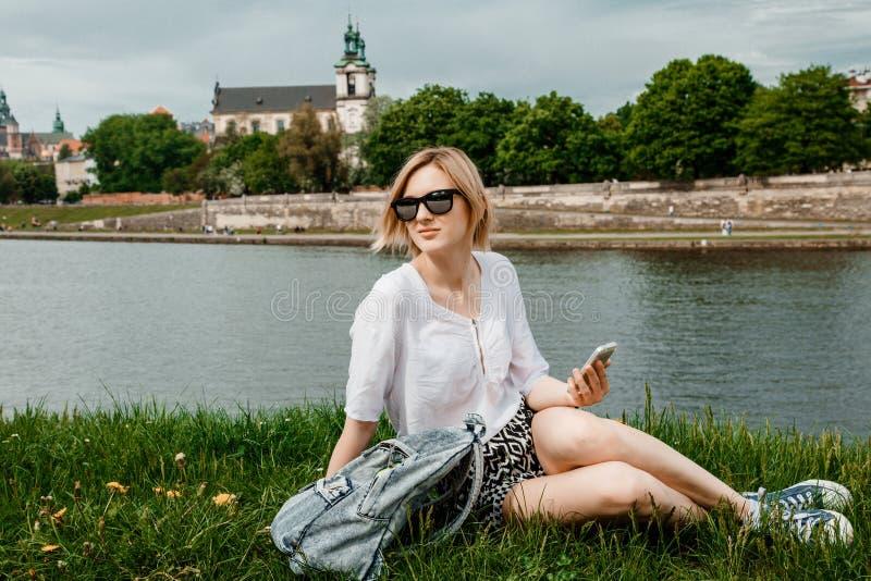 Uma jovem mulher no Vistula River em Krakow A menina à moda nos óculos de sol fala em seu telefone Vista da cidade de Krakow foto de stock royalty free