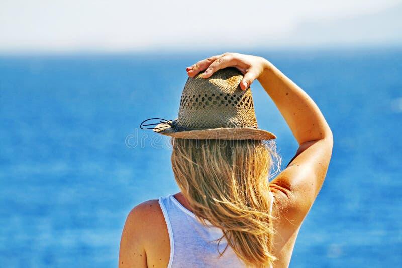 Uma jovem mulher olha pensativamente um mar imagem de stock royalty free