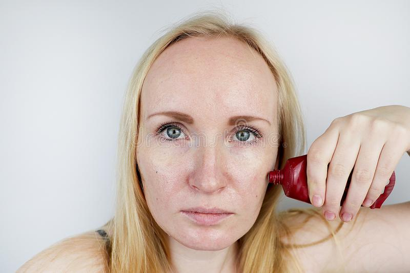 Uma jovem mulher põe uma máscara do gel sobre sua cara Cuidado para oleosa, pele do problema fotografia de stock