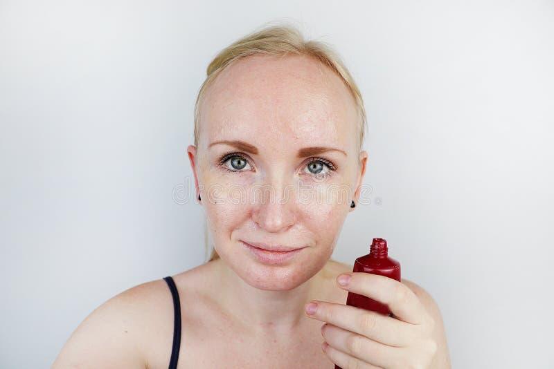 Uma jovem mulher põe uma máscara do gel sobre sua cara Cuidado para oleosa, pele do problema foto de stock