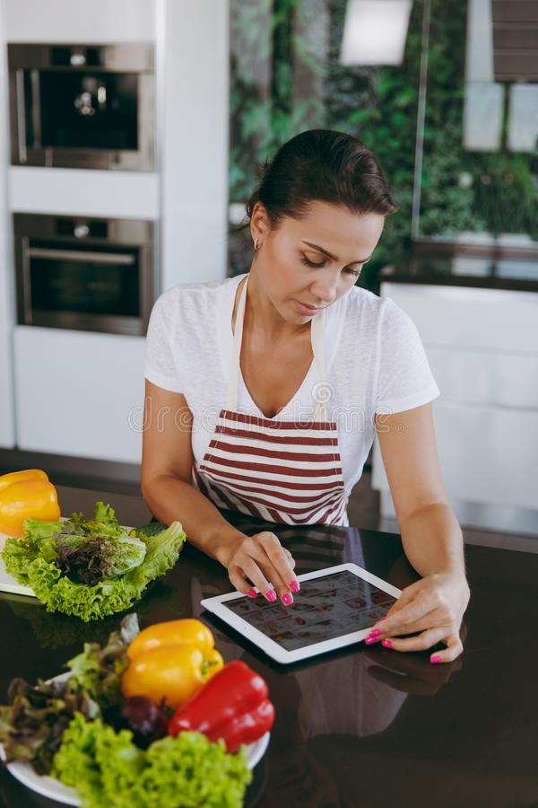 Uma jovem mulher passa o tempo em casa, na cozinha e no roo imagem de stock