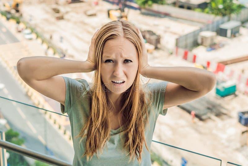 Uma jovem mulher pela janela irritada pela construção trabalha o outsid imagens de stock