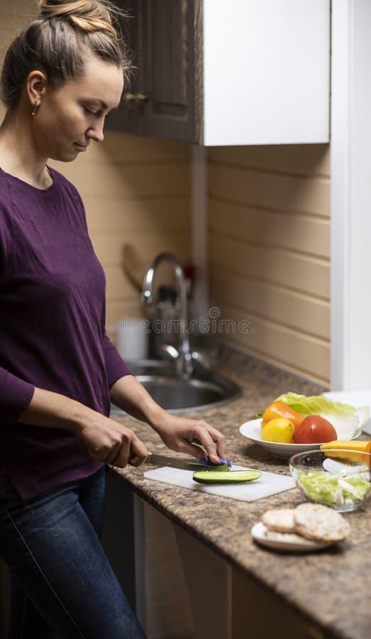 Uma jovem mulher prepara uma salada fotos de stock royalty free
