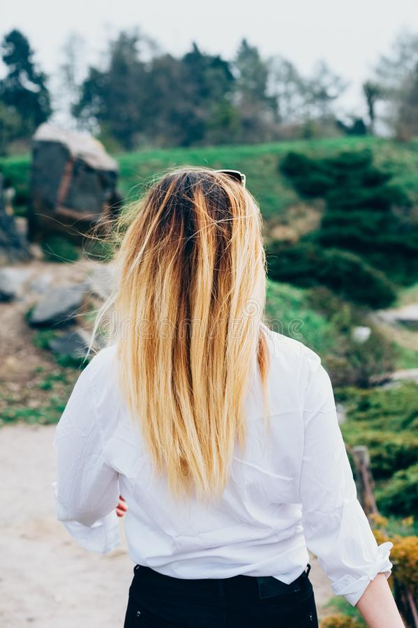 Uma jovem mulher que anda acima do trajeto em um parque, vista traseira fotos de stock royalty free