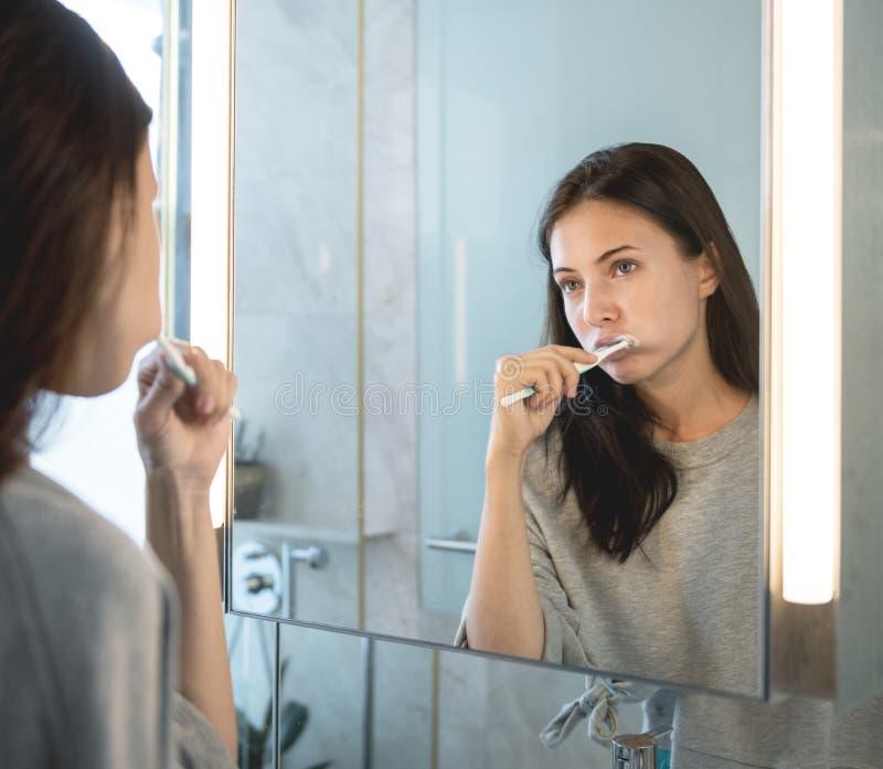 Uma jovem mulher que escova seus dentes na manhã imagem de stock