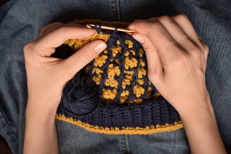Uma jovem mulher que faz crochê um chapéu imagens de stock royalty free