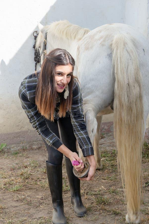 Uma jovem mulher que limpa seus cascos do ` s do cavalo imagens de stock royalty free