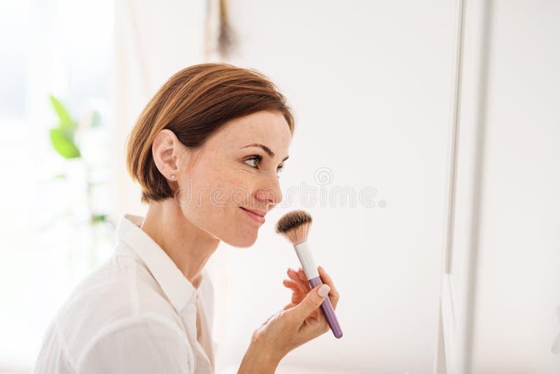 Uma jovem mulher que põe sobre uma composição na manhã em um banheiro foto de stock royalty free