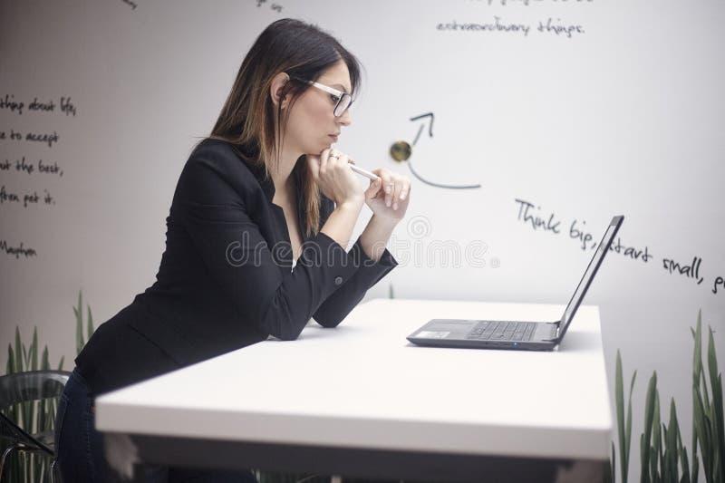 Uma jovem mulher que pensa, 30-39 anos velho, vista lateral, tiro da parte superior do corpo Trabalho no portátil parede com cita imagens de stock royalty free
