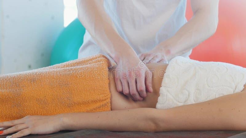 Uma jovem mulher que recebe uma massagem Um massagista que faz massagens o estômago fotos de stock