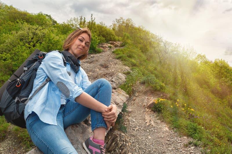 Uma jovem mulher que senta-se em um trajeto da pedra da montanha e que levanta para a câmera Fundos: luz do sol Vista inferior imagens de stock royalty free