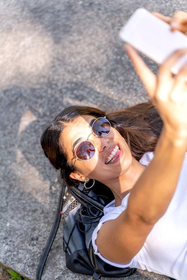 Uma jovem mulher que toma um selfie e que faz as caras engraçadas foto de stock royalty free