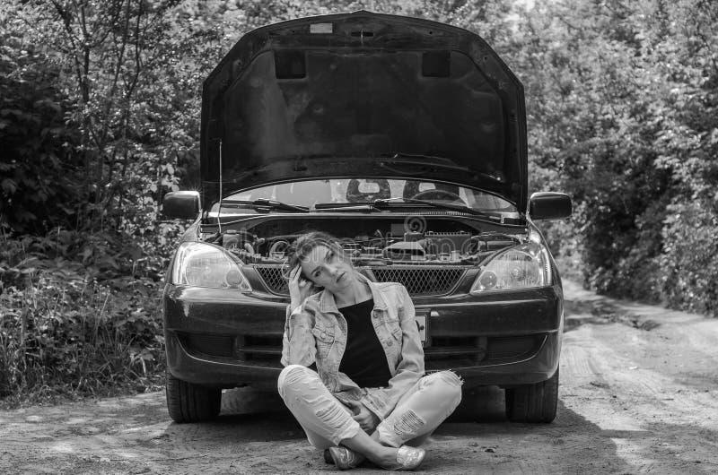 Uma jovem mulher quebrou um carro na estrada e senta-se na frente de um carro com uma capa aberta na confusão e na ajuda de esper fotos de stock