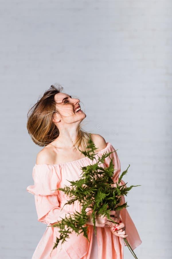 Uma jovem mulher ri e acena seu cabelo contra um fundo branco emocional foto de stock