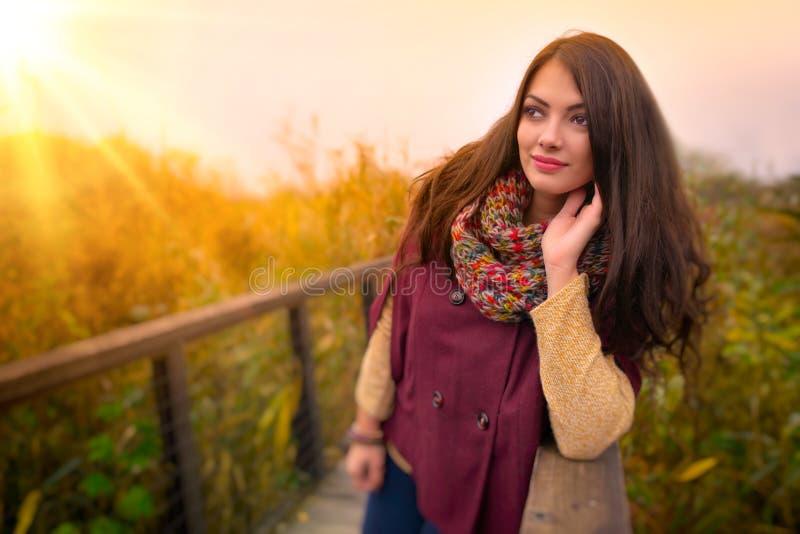 Uma jovem mulher romântica lindo com cabelo marrom longo bonito que aprecia o ar livre do tempo do outono Cabe foto de stock royalty free