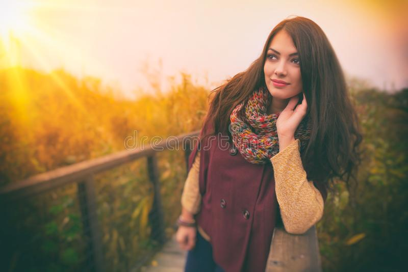 Uma jovem mulher romântica lindo com cabelo marrom longo bonito que aprecia o ar livre do tempo do outono Cabe fotos de stock