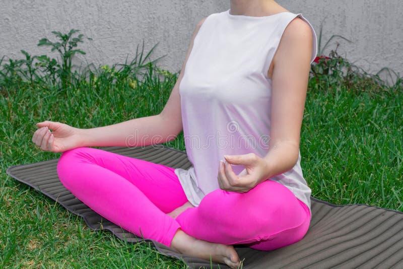 Uma jovem mulher senta-se em uma posição de lótus, pratica a ioga em uma esteira da ioga na grama Close-up, partes do corpo imagem de stock royalty free