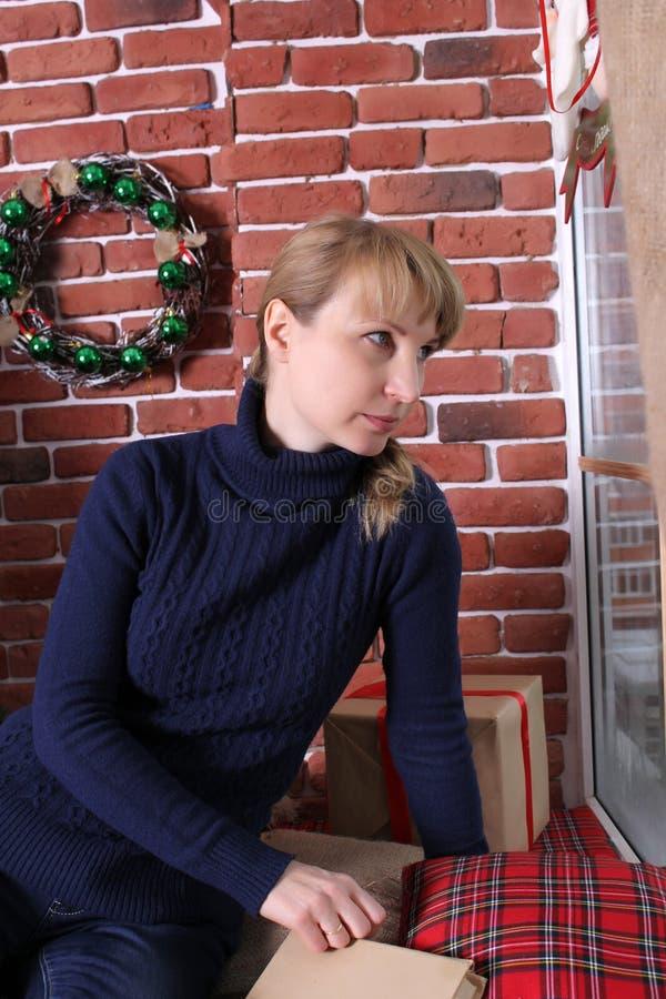 Uma jovem mulher senta-se perto de uma janela Natal fotografia de stock