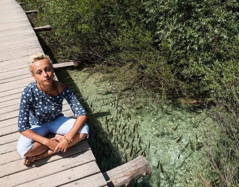 Uma jovem mulher tem um resto, sentando-se com seus pés cruzados, na ponte de madeira sobre um rio claro fotografia de stock