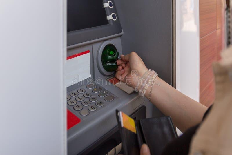 Uma jovem mulher toma o cartão de crédito de um ATM após ter retirado o dinheiro Finança, retirada do dinheiro O terminal exterio fotografia de stock royalty free