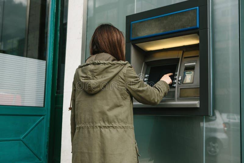 Uma jovem mulher toma o dinheiro de um ATM Agarra um cartão do ATM Finança, cartão de crédito, retirada do dinheiro fotos de stock