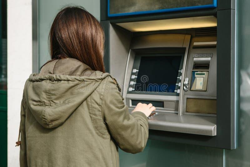 Uma jovem mulher toma o dinheiro de um ATM Agarra um cartão do ATM Finança, cartão de crédito, retirada do dinheiro fotografia de stock royalty free