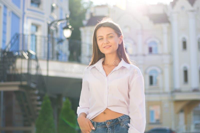 Uma jovem mulher, vestida no estilo ocasional, está em um estreptococo da cidade fotos de stock royalty free