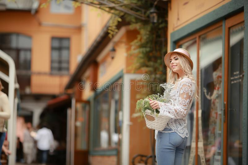 Uma jovem senhora bonita no chap?u do ver?o que descansa caf? ao ar livre na cara sustentada com m?o e o amigo de espera fotografia de stock royalty free