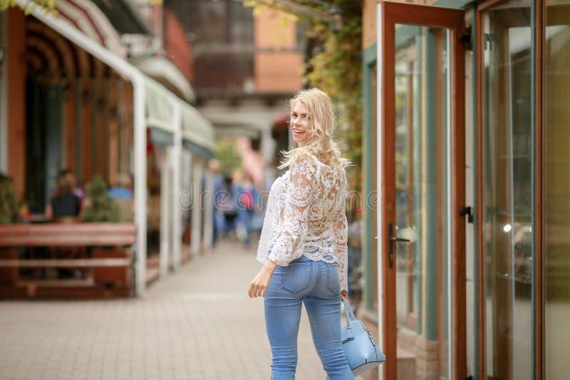 Uma jovem senhora bonita no chap?u do ver?o que descansa caf? ao ar livre na cara sustentada com m?o e o amigo de espera foto de stock royalty free